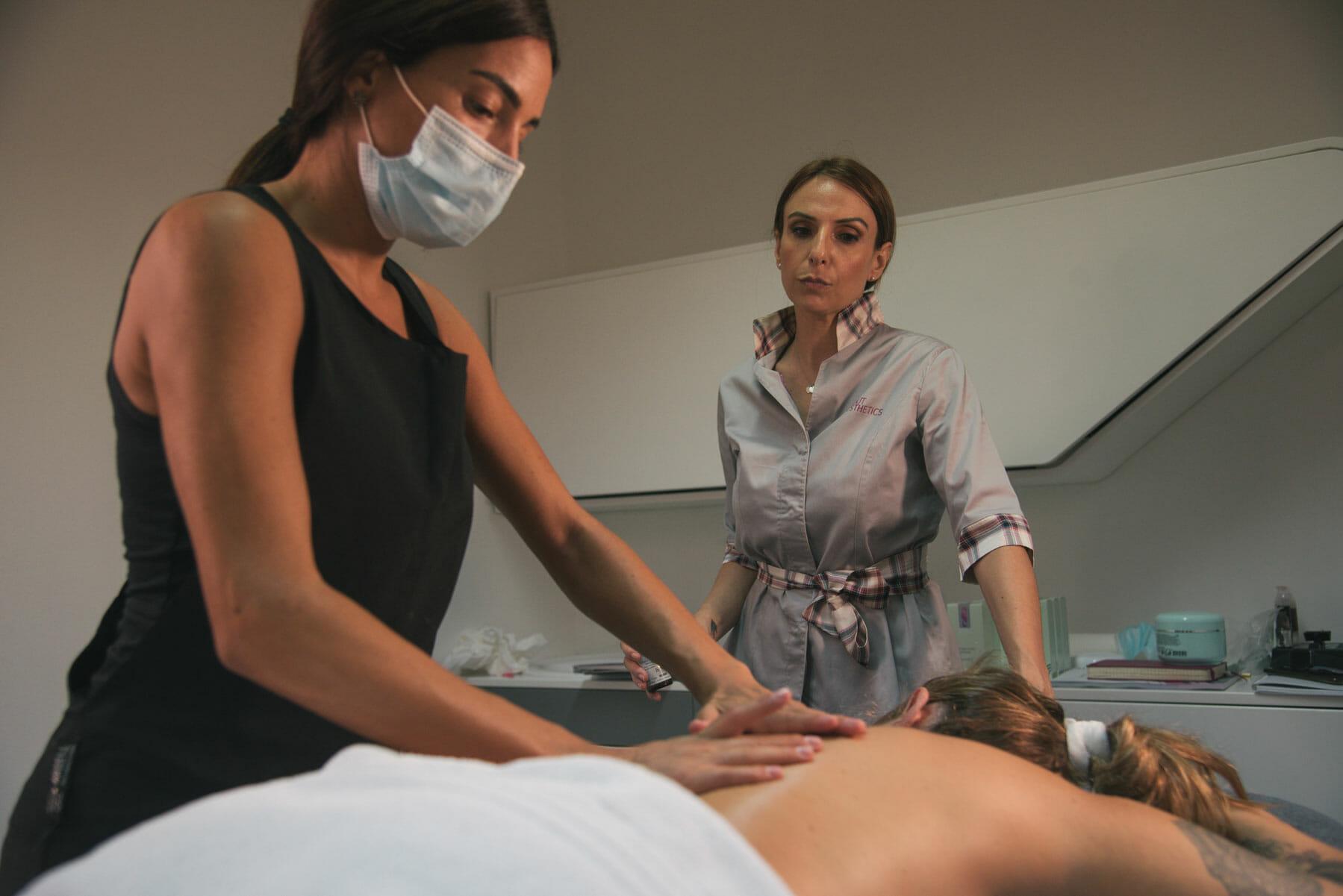 Sono rappresentate Ilaria che spiega come fare un massaggio personalizzato ad una sua allieva. Si vede l'allieva stessa che sta massaggiando una cliente.